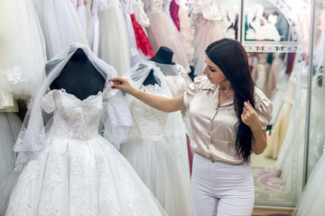 Beautiful brunette bride choosing dress for wedding