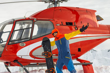 Snowboarder Freerider Is Standing At The Helicopter In The Snowy Mountains In Winter Under The Clouds
