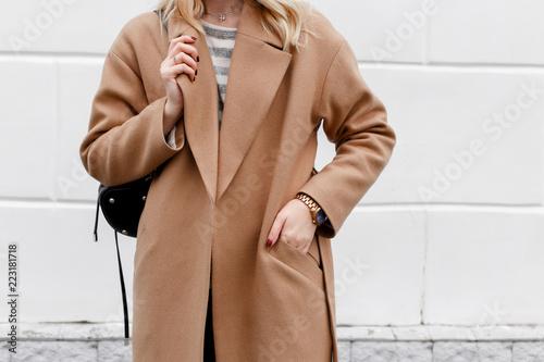 Fototapeta Beautiful young stylish blonde woman wearing beige coat and black backpack posing near white street wall