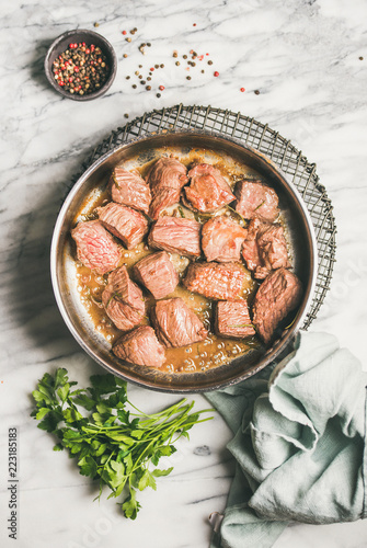 Meat dinner. Flat-lay of braised beef meat stew with fresh parsley in cooking pan over white marble table background. Comfort winter food