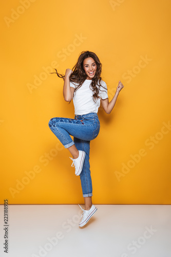 Obraz Full length portrait of a cheerful girl with long dark hair - fototapety do salonu
