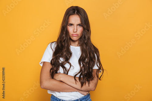 Fotografía  Photo of resented woman in casual clothes standing with arms folded, isolated ov