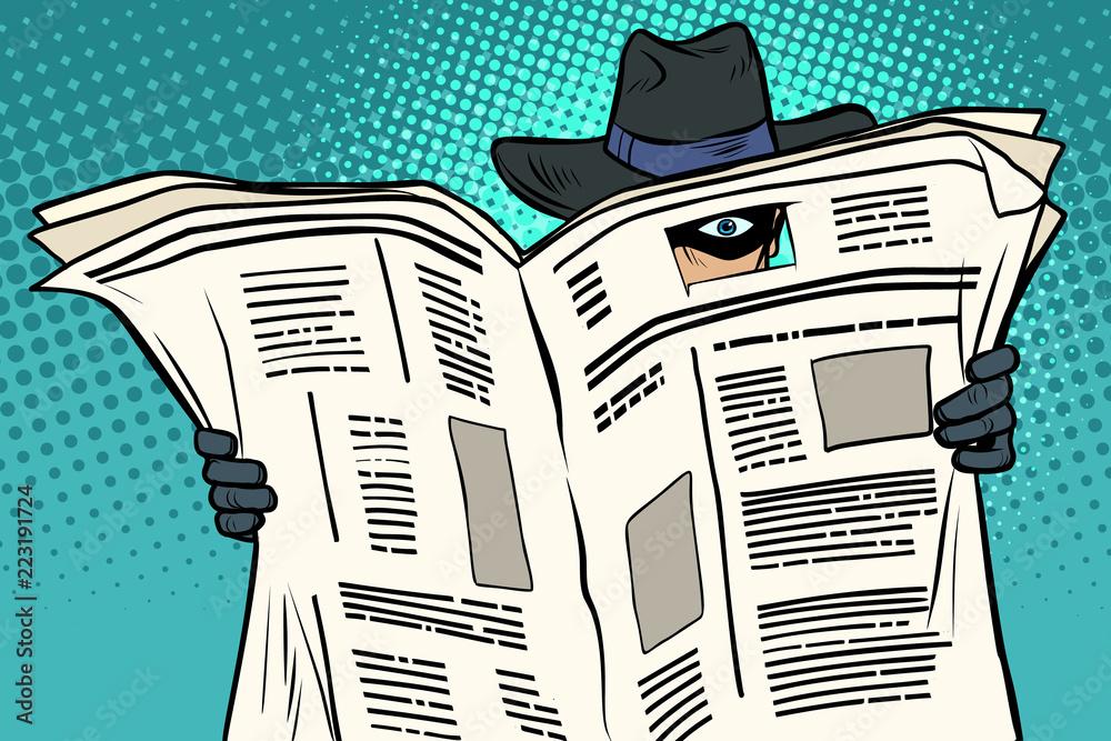 Fototapeta spy watches through the newspaper