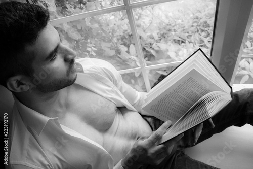 Valokuva  Man in sitting on window ledge with open shirt and pecs reading hardback book