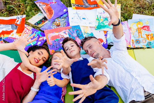 Papiers peints Attraction parc Smiling creative family paitners of mother, father, and two children in aprons lying down on grass with drawings outside having fun with arms and hands outstrectched to the camera.