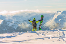 Snowboarder Freerider Is Standing In The Snowy Mountains In Winter Under The Clouds