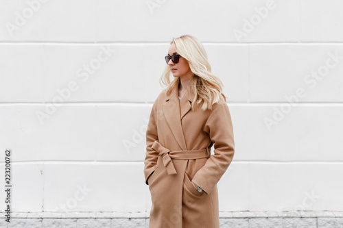 Obraz na plátně Beautiful young stylish blonde woman wearing beige coat and black sunglasses standing near white street wall