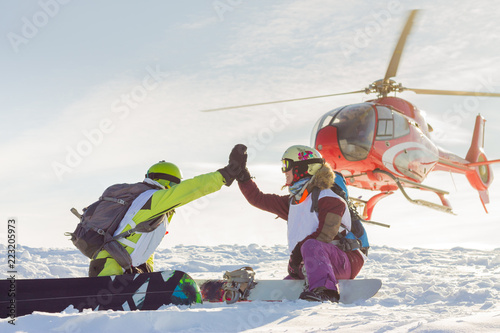 fototapeta na ścianę pair of freeriders of snowboarders give five when the helicopter lands