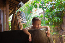 Happy Baby Son With Mother Have Fun In Bath. Playful Woman Spraying Child From Shower In Outside Bathroom On Open Veranda With Beautiful Tropical Garden View In Luxury Villa On Summer Family Vacation.
