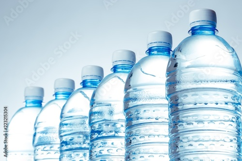 Six Water Bottles in a Row on the Blue Background