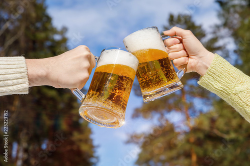 Tuinposter Bier / Cider Friends clinking with beer mugs .