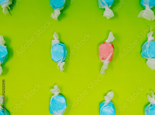 Blue and red taffy candy on bright green background, shows being different with food color.