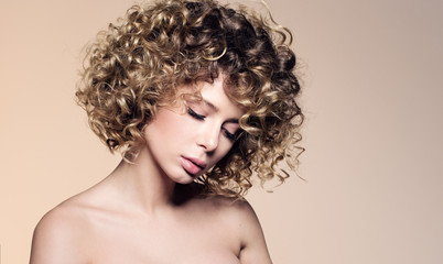 Beauty portrait of beautiful young woman with closed eyes. Hairstyle with curly hair. Professional make-up, delicate clean skin