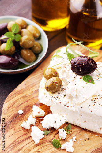 Greek cheese feta with herbs and olives on rustic table.