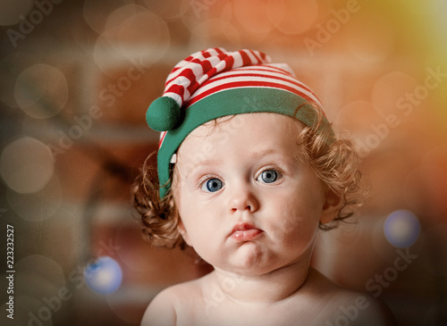 aa90cbfac439a Little baby boy in elf hat with Christmas fairy lights on background. Christmas  time season image