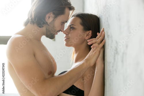 Sensual couple holding hands looking in the eyes leaning on wall, passionate lov Fototapeta