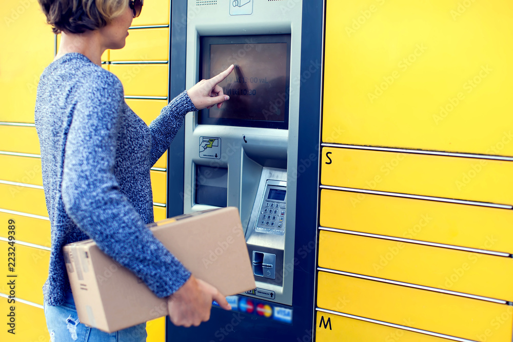 Fototapeta Woman using automated self service post terminal machine or locker to deposit the parcel for storage
