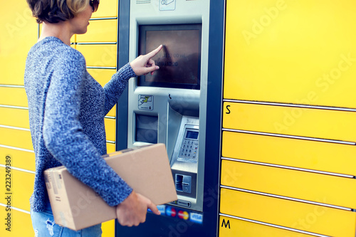 Fotografija  Woman using automated self service post terminal machine or locker to deposit th