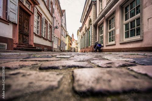 Fototapeten Schmale Gasse Old European cobblestone street from low perspective, Heidelberg Germany