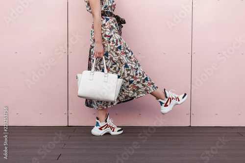 Fotografia  Stylish beautiful young woman in fashionable dress with stylish white bag and trendy sneakers is near the pink wall