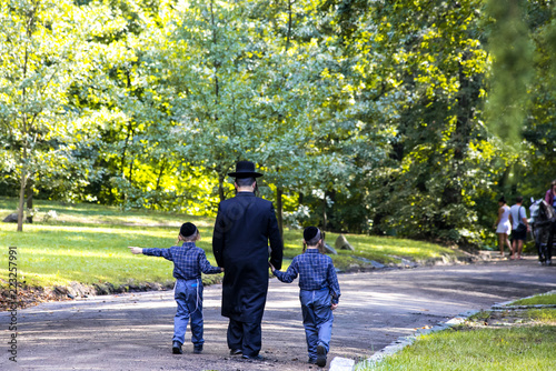 A family of Hasidic Jews, a man with children, walks through the Autumn Park in Uman, Ukraine, during the Jewish New Year,  Religious Orthodox Jew