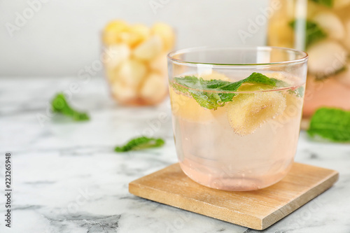 Glass with tasty melon ball drink on table