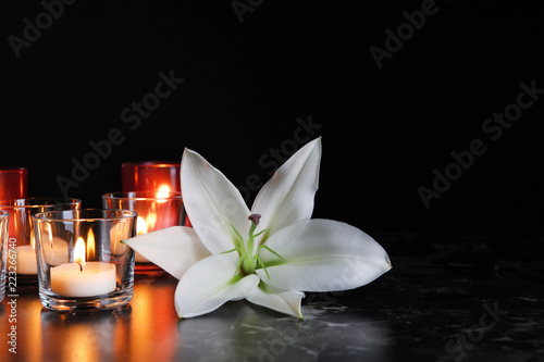White lily and burning candles on table in darkness, space for text. Funeral symbol