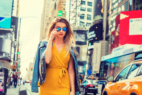 Photo  Young Eastern European Woman traveling in New York, with long brown hair, wearing yellow dress, blue Denim jacket draped over shoulder, blue sunglasses, walking on street in Times Square of Manhattan