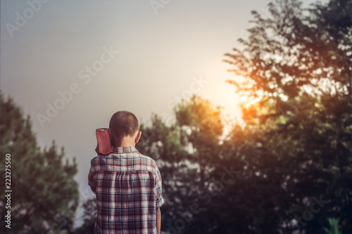 Fotografia, Obraz Boy raised the Bible on shoulder with ligtf of sunset in mountain background