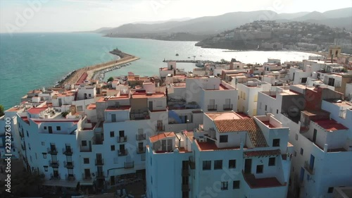 White houses and roofs of the Spanish city Peniscola. Aerial drone view. Province of Castellon, Valencian Community, Spain. Zoom out