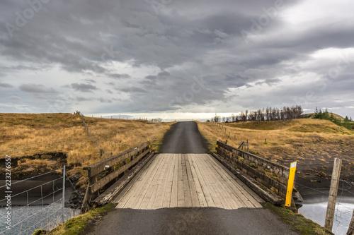 Fotografia  A countryside bridge in a cloudy, dark day in Iceland