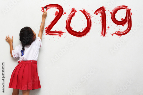 Fotografie, Obraz  Little girl holding a paint brush painting happy new year 2019 on a white wall b
