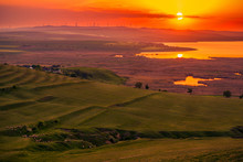 Sun Setting Over A Field Of Eolian Wind Turbines And A Valley With A Lake And A Herb Of Sheep