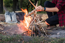 Making Campfire At A Forest. Going Into The Wild Concept: Camping Place With Vintage Backpack, Thermos And Male In Casual Clothes Puts Pieces Of Wood Into Fire.