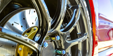 Polished mag wheel with blue bolt caps of a car