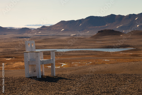 Poster Diepbruine Creative large wooden chair on a stony rocky desert landscape of Iceland