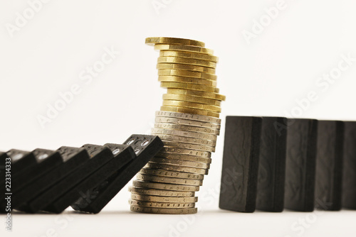 Photo  Financial crisis concept with pile of cash money under domino effect, white back