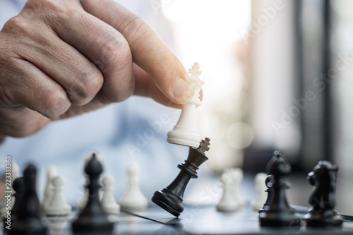 Photo  Businessman's hand playing chess game to development analysis new strategy plan,