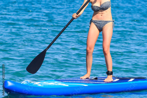 Young beautiful woman in a bikini on a SUP board in the sea. Adventure girl on Standup paddleboarding with a paddle in the ocean. Back view.