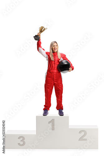 Female racer on a winner's pedestal with gold trophy cup