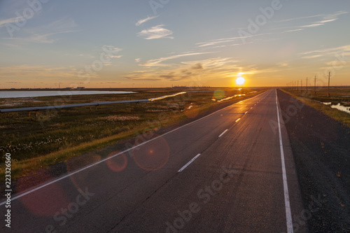 Beautiful sunset on the background of an asphalt road