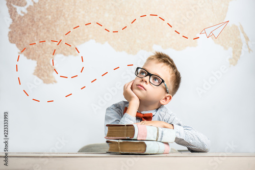 Photo  A dreamy schoolboy sits at a desk with books, wears glasses