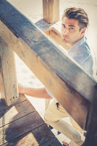Staande foto Kapsalon Handsome guy with trendy hairstyle going down wooden stairs while looking. Warm intense summer lights, wooden structure.