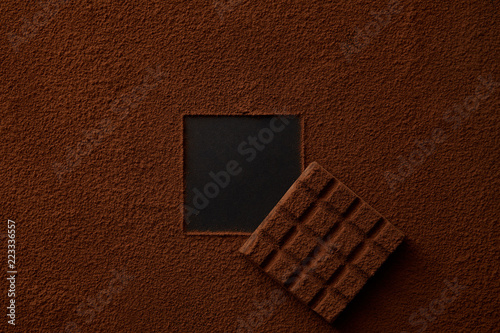 gourmet cocoa powder with square copy space and chocolate on black background Fototapeta