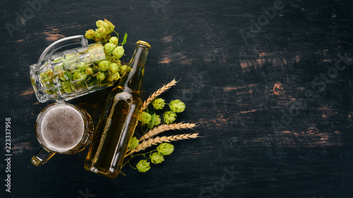 Beer and fresh hops on a black wooden background Poster Mural XXL