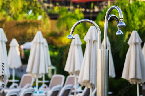 Poster Oceanië white modern deck chairs with umbrellas nearby them and a metal unusual shower standing outdoor the hotel