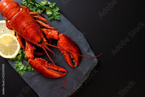 Fototapeta lobster with vegetable and lemon on black slate plate