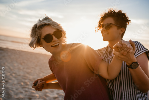 Fotografía Laughing lesbian couple dancing together on a beach at sunset