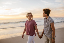 Smiling Lesbian Couple Walking Along A Beach At Sunset