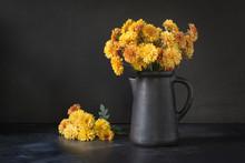Autumn Dark Still Life. Fall With Yellow Chrysanthemum Flowers In Clayware Vase On Black.